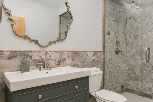 bathroom remodel with gray vanity and stone mosaic tile