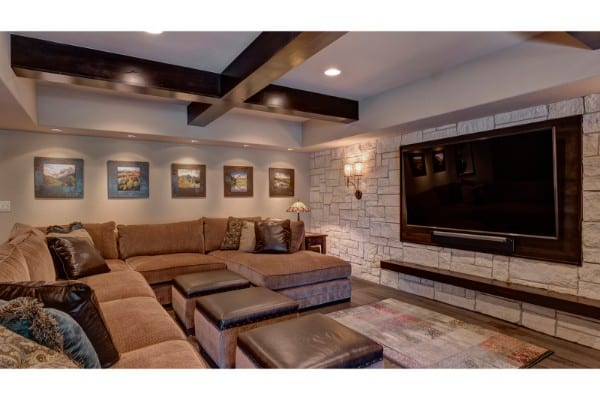 basement remodel with home theater | stone wall and wood ceiling beams