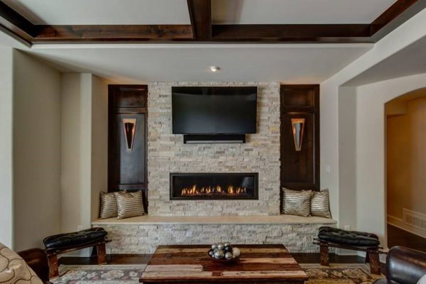 basement remodel with stone wall fireplace and home theater